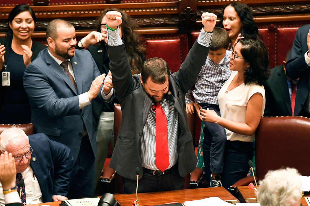 Sen. Luis R. Sepulveda (center) celebrates after the Green Light Bill granting was passed by the state Senate.