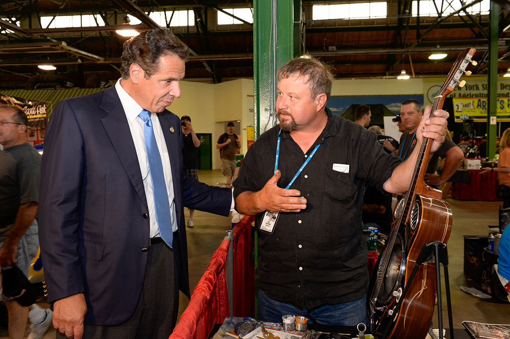 Andrew Cuomo looking at a guitar.