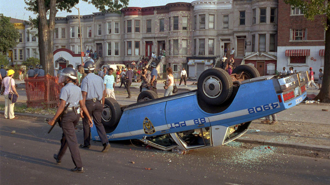 Police in riot gear walk past a police car that was overturned by rioters in the Crown Heights section of the Brooklyn borough of New York, where racial violence flared for days.
