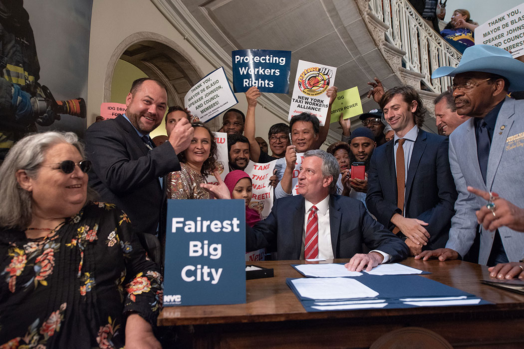 New York City Mayor Bill de Blasio signs legislation last year to cap for-hire vehicles and mandate a minimum wage for drivers.