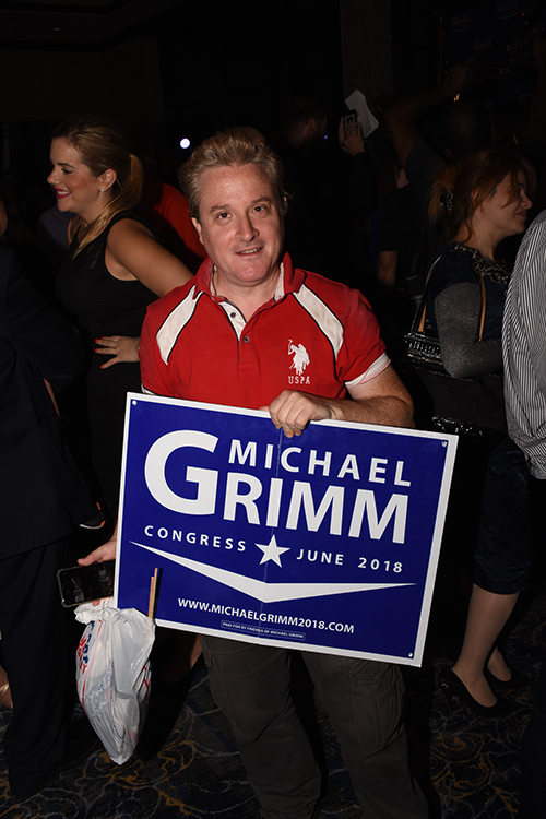 a man holds a Michael Grimm sign.