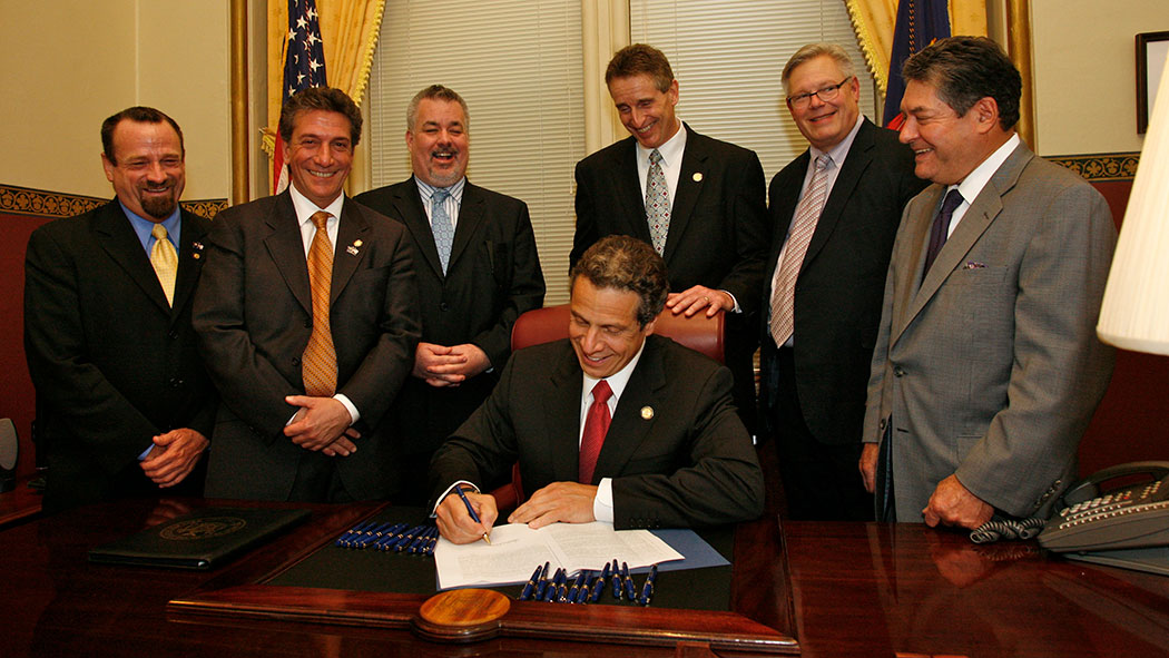 Gov. Andrew Cuomo signing the Marriage Equality Act, with Harry Bronson, Matthew Titone, Daniel O'Donnell, Bob Duffy, Tom Duane and James Alesi.